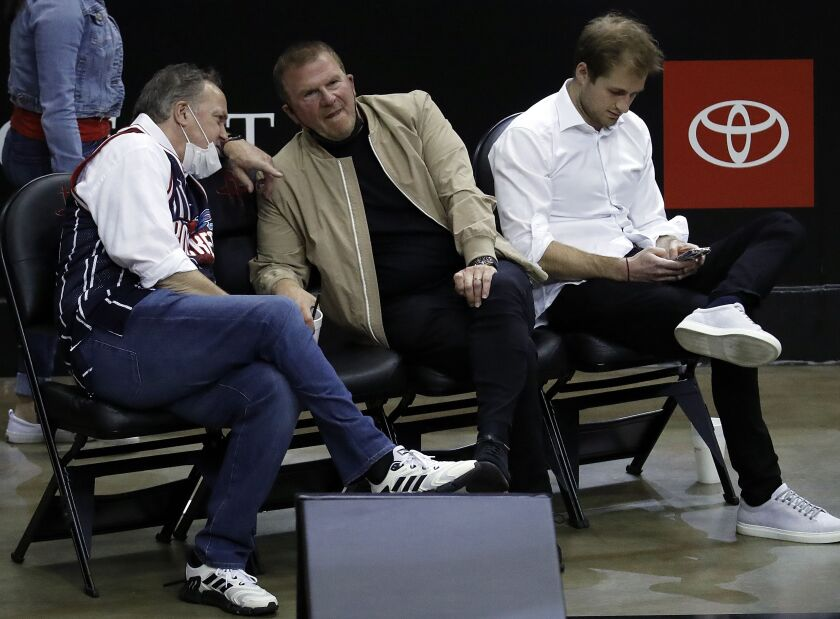 Houston Rockets owner Tilman Fertitta, center, team president Tad Brown, left and Patrick Fertitta sit courtside as the Rockets played the Los Angeles Clippers in an NBA basketball game Friday, May 14, 2021, in Houston. (Bob Levey/Pool Photo via AP)