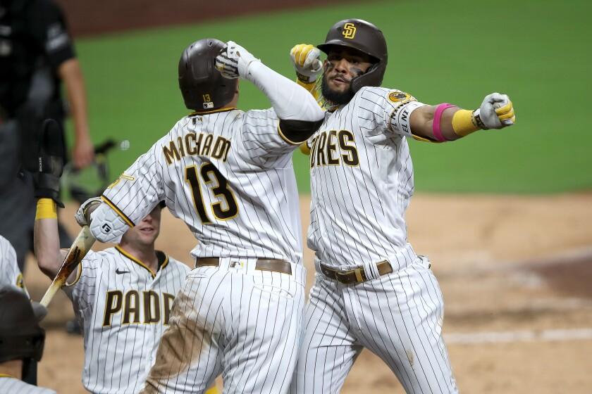 The Padres' Manny Machado congratulates Fernando Tatis Jr.