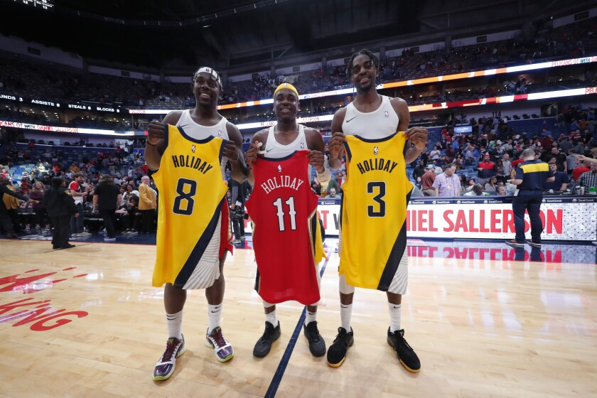 Pelicans guard Jrue Holiday, left, swaps jerseys with brothers Aaron, center, and Justin, who play for the Pacers, on Dec. 28, 2019, in New Orleans.