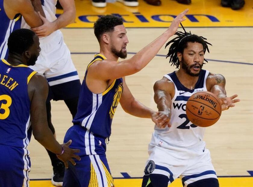 El jugador de los Timberwolves de Minnesota Derrick Rose (dcha) pasa el balón ante la defensa de Klay Thompson (c), de los Warriors de Golden State, durante un partido. EFE/Archivo