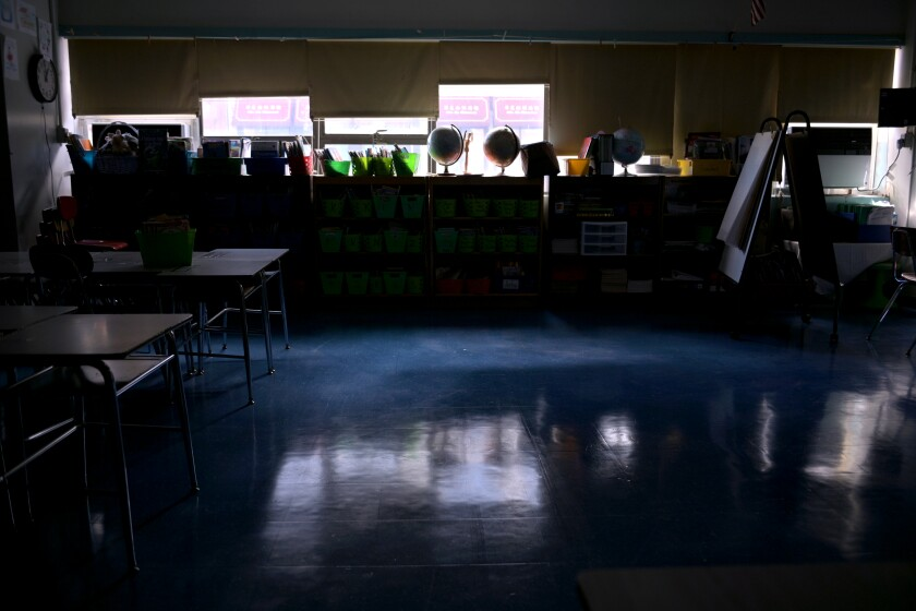 A classroom is empty with the lights off.