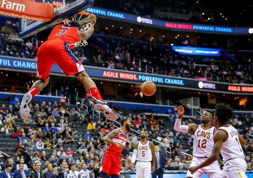 Washington Wizards guard Bradley Beal (L) hangs on the rim after dunking against the Cleveland Cavaliers during the first half of the NBA basketball game between the Cleveland Cavaliers and the Washington Wizards at Capital One Arena in Washington, DC, USA, 14 November 2018. EPA-EFE/ERIK S. LESSER