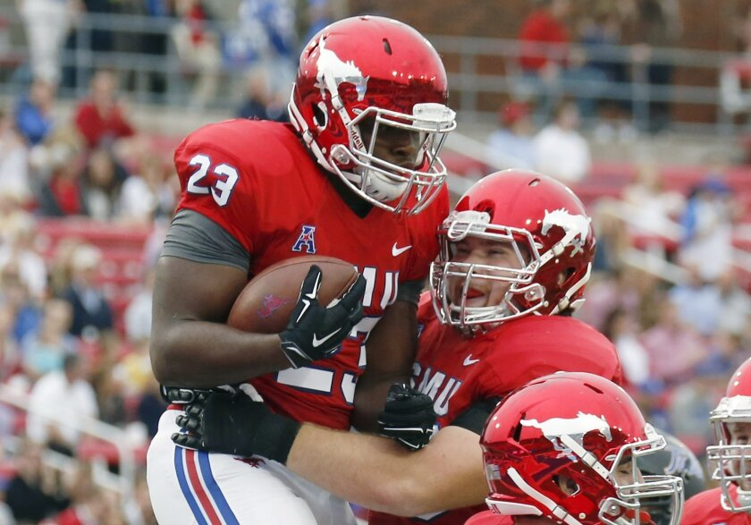 SMU tight end Jeremiah Gaines (23) celebrates his touchdown with offensive lineman Evan Brown against Tulsa during the first half of an NCAA college football game, Saturday, Oct. 31, 2015, in Dallas. (AP Photo/Jim Cowsert)
