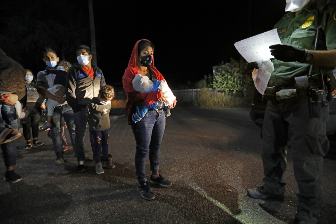 A line of migrant adults and children standing before a Border Patrol agent at night.