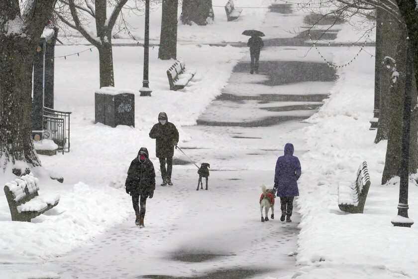 Pedestrians walk along a snow-covered path in the Boston Common, Tuesday, Feb. 9, 2021, in Boston. (AP Photo/Steven Senne)
