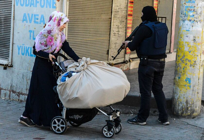 A woman passes a government soldier during clashes in central Diyarbakir, Turkey, on March 17.