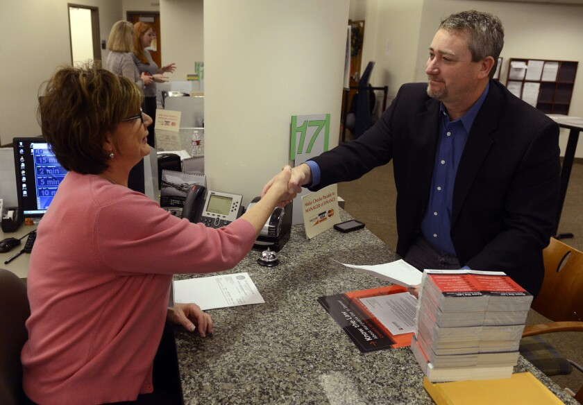 Shawn Phillips, right, owner of Strainwise marijuana stores, shakes hands with Jennifer Scott of the Denver Excise and License office after receiving his license to legally sell marijuana in the city.