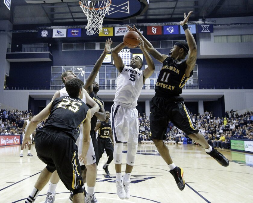 Xavier's Trevon Bluiett (5) attempts a shot after rebounding against Northern Kentucky's Lavone Holland II (11) and Cole Murray (25) in the second half of an NCAA college basketball game Monday, Nov. 23, 2015, in Cincinnati. Xavier won 78-66. (AP Photo/John Minchillo)