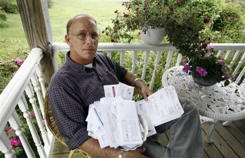 Carpenter Greg Douglas sits with dozens of medical bills at his home in Harpswell, Maine, on Wednesday, July 1, 2009. The community held a benefit for him and put out collection cans to help with medical expenses after he was injured when his truck rolled on black ice. (AP Photo/Pat Wellenbach)