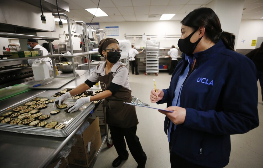 UCLA food service employees at work in a kitchen.