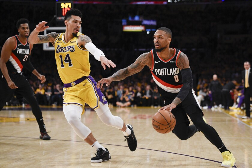 Portland guard Damian Lillard  drives to the basket in front of Lakers guard Danny Green during the Trail Blazers' win Friday.