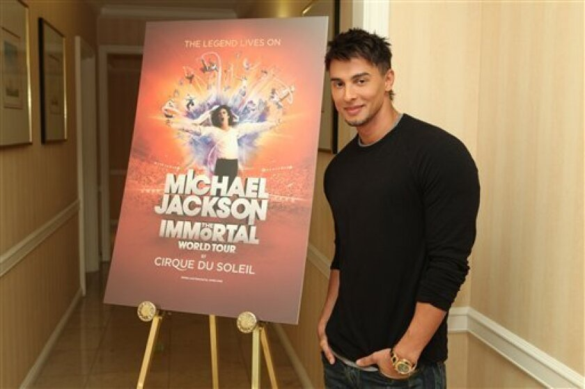 """In this publicity image released by Cirque du Soleil, Jamie King, writer and director of """"Michael Jackson The Immortal World Tour"""" by Cirque du Soleil, stands by a promotional poster, Wednesday, Nov. 3, 2010 in Los Angeles where the Estate of Michael Jackson and Cirque du Soleil announced the launch of the production combining Michael Jackson music and choreography with Cirque du Soleil performers. The tour begins in October 2011 in Montreal. (AP Photo/Cirque du Soleil, Jake Novak)"""