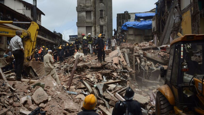 Rescue workers look for survivors in the debris of a collapsed building in Mumbai, India, on Aug. 31