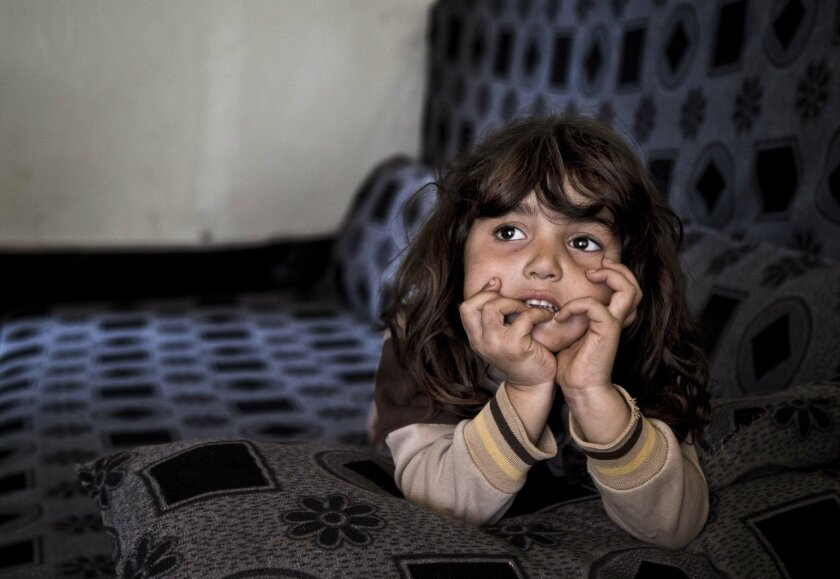 In this Saturday, Nov. 28, 2015 photo, Syrian refugee Simav Nuh, rests inside an informal tented settlement in Irbil, northern Iraq. Some 240,000 refugees who fled the fighting in Syria now live in Iraq. Their children are neither citizens of Syria, their families' country of origin, or of Iraq, the country where they now live. (AP Photo/Seivan M. Salim)