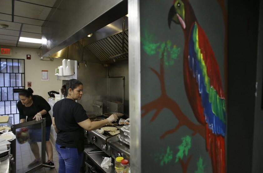La salvadoreña Anna López (zq) y la hondureña María Erazo trabajando en la cocina de un restaurante de Chelsea, Massachusetts, el 27 de junio del 2019. Activisats temen que el gobierno de EEUU está usando tecnología de reconocimiento facial para pillar personas que están en el país si permiso de residencia. (AP Photo/Steven Senne)