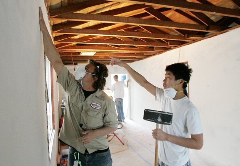 """High Tech High instructor Josh Saxe and student Hung Ha, 16, sanded plaster together on Wednesday during their class on home design. """"This is a way to tie in learning with real-life experience,"""" Saxe said."""