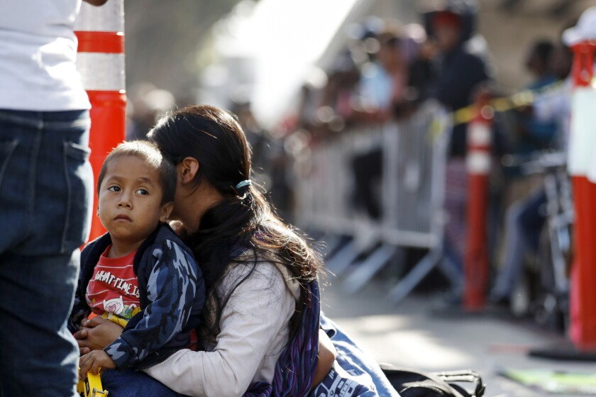 A woman sits with her sons as they wait to apply for asylum in the U.S. along the border in Tijuana, Mexico.