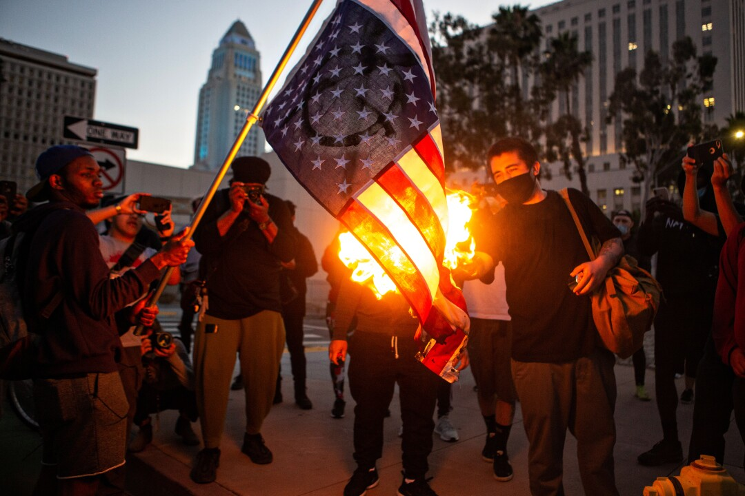 Protesters in downtown Los Angeles burn an American flag to protest the killing of George Floyd by police in Minneapolis.