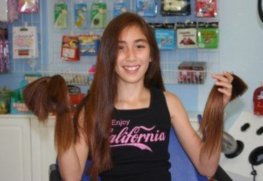 Grace shows off the newly trimmed hair she is donating. Photo by Kristina Houck
