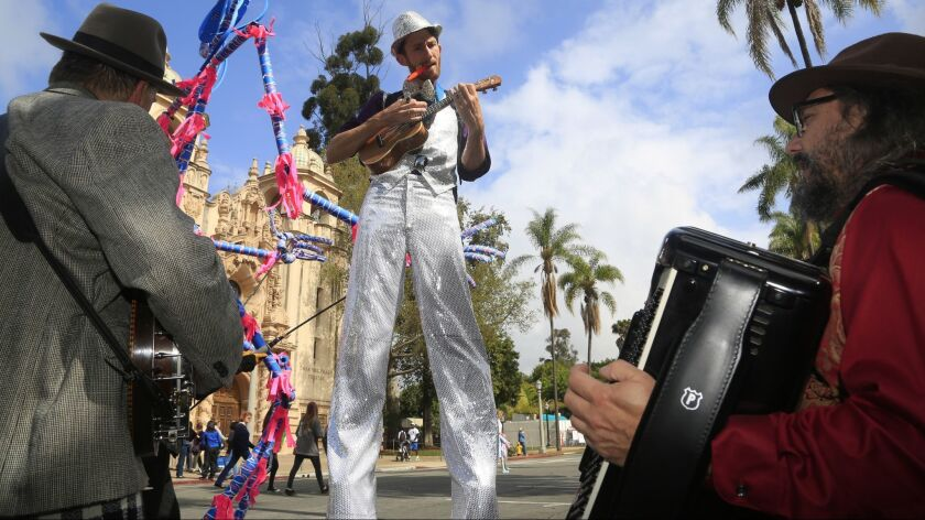 """Fern Street Circus performers John Highkin on banjo, left, """"Bags"""" on ukelele, center, and Mark Danisovszky on accordion tuned their instruments before the start of the Kids Floral Wagon Parade. The day long event, Garden Party of the Century is part of t"""