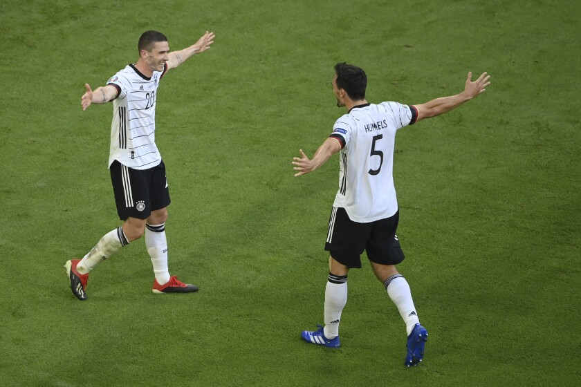 Germany's Robin Gosens, left, celebrates Germany's Mats Hummels after scoring his side's fourth goal during the Euro 2020 soccer championship group F match between Portugal and Germany at the football arena stadium in Munich, Saturday, June 19, 2021. (Matthias Hangst/Pool Photo via AP)