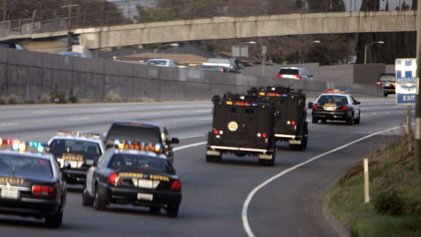 Police cars and SWAT vehicles pursue a fleeing motorist on the 710 Freeway.