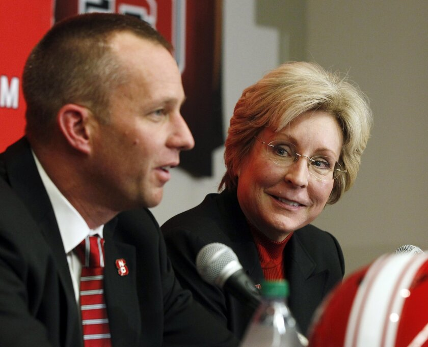 FILE - In this Dec. 2, 2012, file photo, North Carolina State athletic director Debbie Yow, right, listens as football head coach Dave Doeren speaks during a news conference in Raleigh, N.C. Yow has guided the Wolfpack within a step or two of her stated goal of building a national top-25 program. (