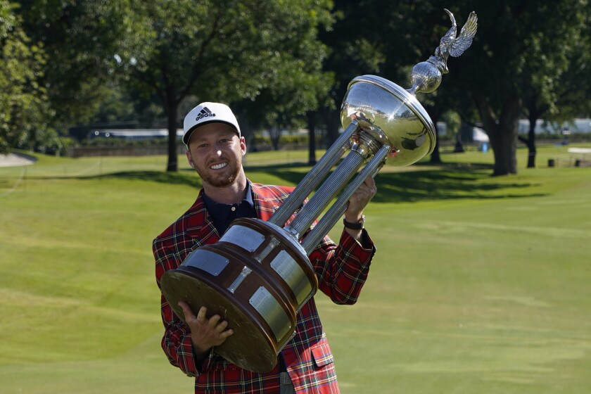 Daniel Berger poses with the championship trophy after winning the Charles Schwab Challenge.