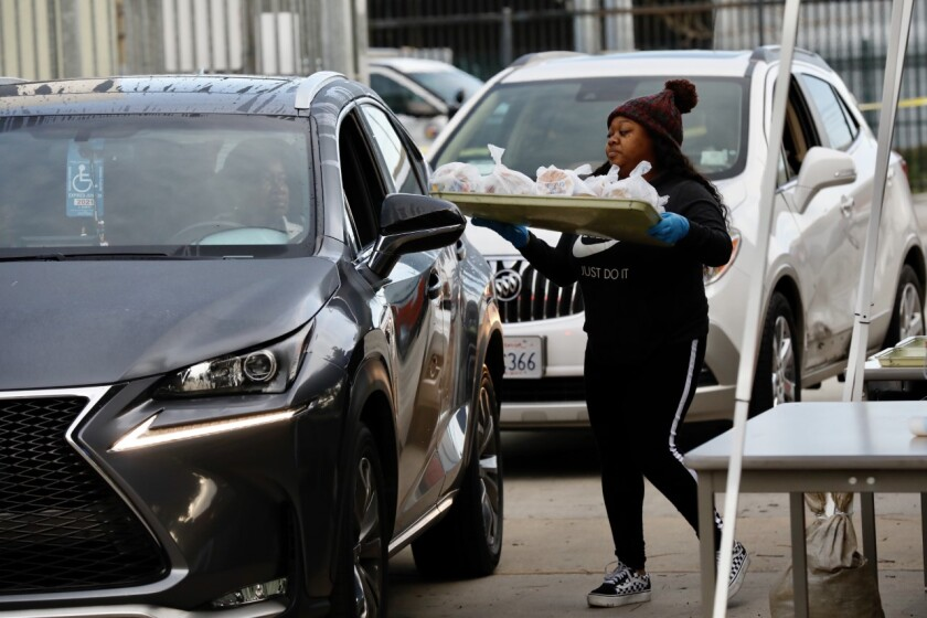 LAUSD volunteer Courtney Johnson delivers food to vehicles at Dorsey High School in Los Angeles this month. Pasadena schools have suspend their grab-and-go program after a kitchen worker fell ill.