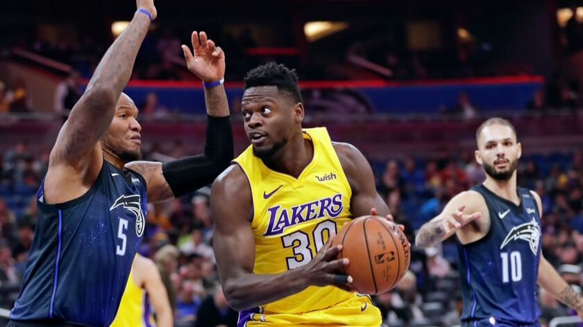 The Lakers' Julius Randle looks for a shot as he gets between the Orlando Magic's Marreese Speights, left, and Evan Fournier during the first half of Wednesday's game.