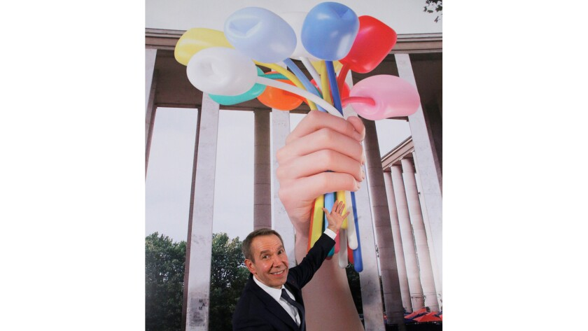 Jeff Koons poses next to a rendering of his proposed sculpture during an event at the American Embassy in Paris.