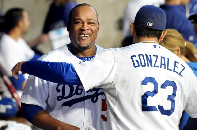Dodgers infielder Juan Uribe gets a hug from first baseman Adrian Gonzalez as they prepare to play the San Francisco Giants last summer at Dodger Stadium.