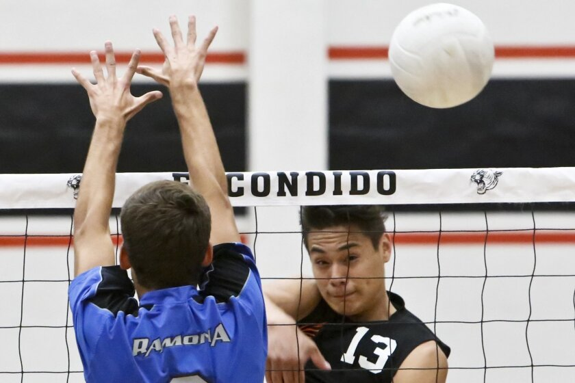Escondido's Mario Lucas (13) — who had 17 kills, one block and one ace in the match — drives a shot past Ramona's Isaiah Spieker. The Cougars defeated the Bulldogs to improve their record to 6-0 in the Valley League.