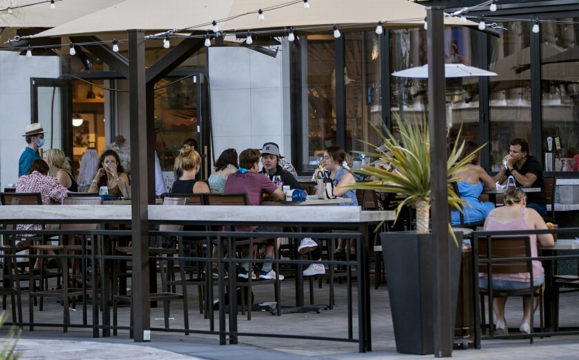 Unmasked customers sit on an outdoor patio