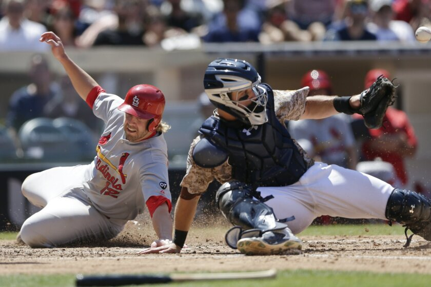 The Cardinals' Mark Reynolds, left, slides in safely to home, scoring on a sacrifice fly by Matt Carpenter, as San Diego Padres catcher Austin Hedges misses the throw during the fourth inning of a baseball game Sunday, Aug. 23, 2015 in San Diego.