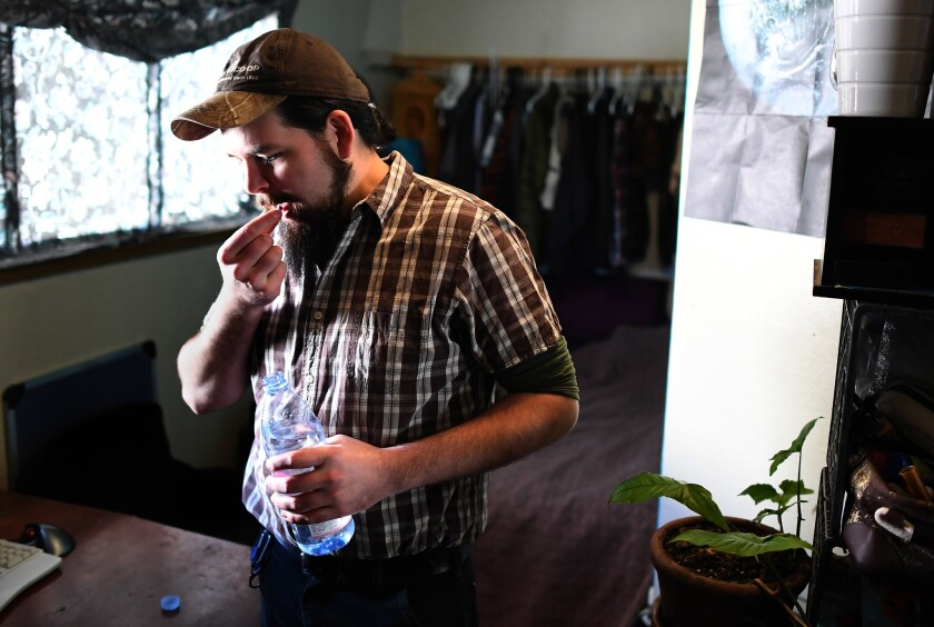 Rand Hunt takes pre-exposure prophylaxis, or PrEP, medication in his bedroom in Oakland on a recent morning. Hunt, 34, who was born the year HIV was identified, has lived his entire life in the shadow of the AIDS epidemic.