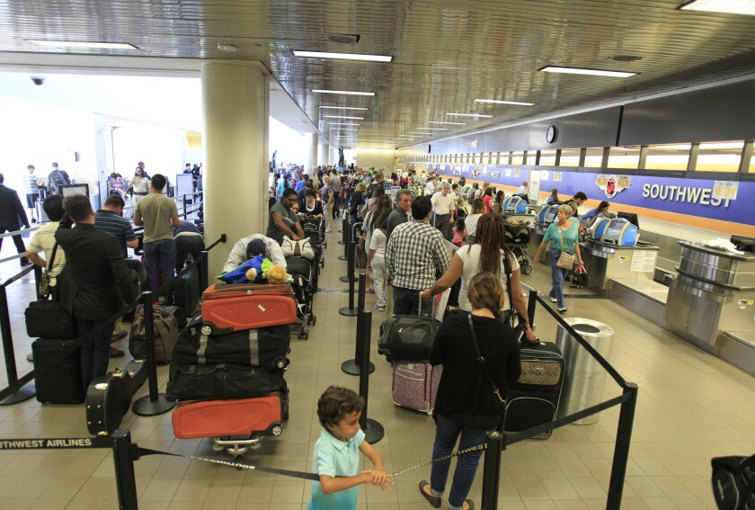Travelers line up at the Southwest Airlines ticketing counter at Los Angeles International Airport last year. A report from the FAA says demand for air travel will grow an average annual rate of 2.5% over the next 20 years.