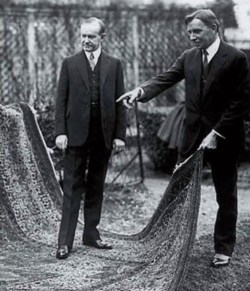 President Coolidge is pictured standing on a rug woven by orphans of the Armenian genocide with Near East Relief Vice-Chairman Dr. John Finley. The rug goes on display today at the White House.