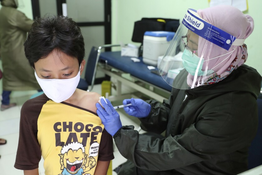 An elementary school student, wearing a face mask as a precaution against the coronavirus outbreak, receives a Td vaccine shot from a health worker during a free vaccination service for schoolchildren in Jakarta, Indonesia,Tuesday, Oct. 27, 2020. (AP Photo/Achmad Ibrahim)
