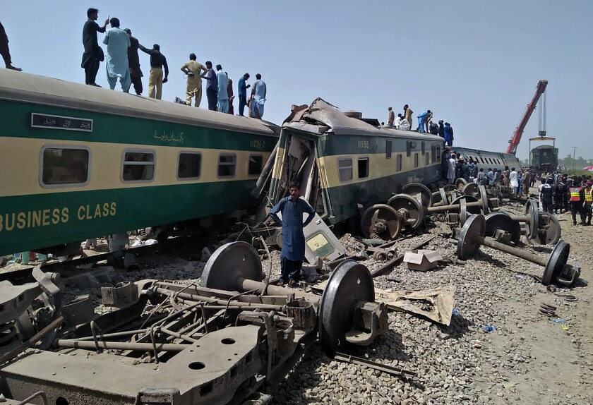 Soldiers and volunteers work at the site of a train collision in Ghotki district in southern Pakistan, Monday.