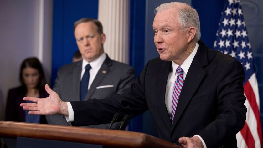 Attorney General Jeff Sessions, right, accompanied by White House press secretary Sean Spicer, talks