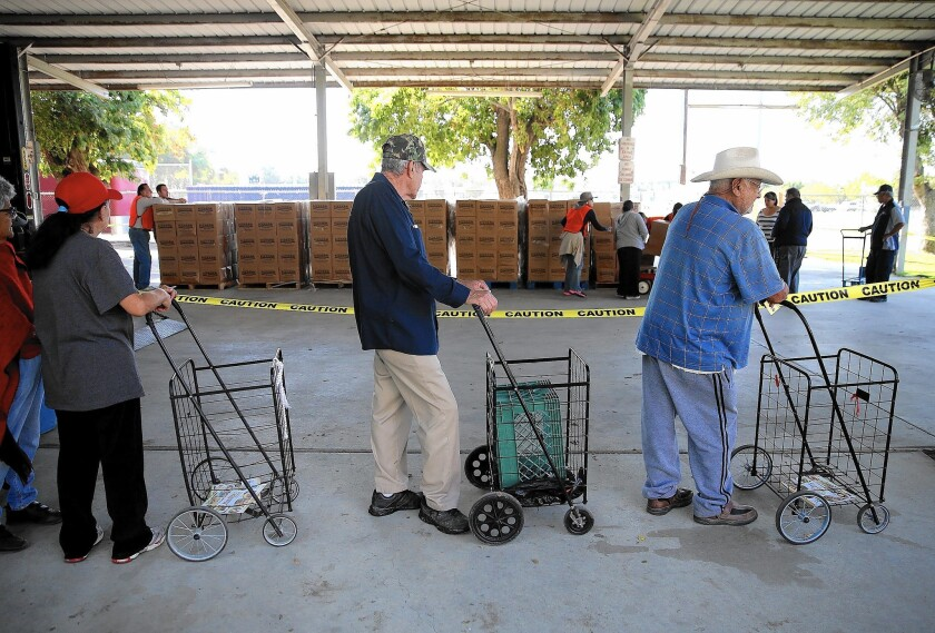 People line up with carts during a food giveaway for the needy in Firebaugh, Calif.