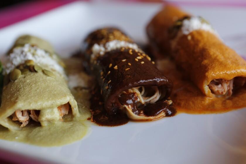 Enchiladas Tres Moles (de pollo o queso), smothered in mole poblano, red, and green sauces, at La Casita Mexicana in Bell.