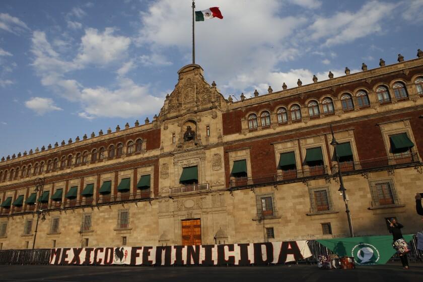 Una manta que denuncia los feminicidios en México yace desplegada frente al Palacio Nacional el miércoles 25 de noviembre de 2020 durante una marcha por el Día Internacional de la Eliminación de la Violencia Contra las Mujeres, en la Ciudad de México. (AP Foto/Ginnette Riquelme)
