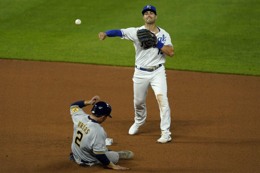 Kansas City Royals second baseman Whit Merrifield throws to first for the double play hit into by Milwaukee Brewers' Pablo Reyes after forcing Luis Urias (2) out at second during the sixth inning of a baseball game Tuesday, May 18, 2021, in Kansas City, Mo. (AP Photo/Charlie Riedel)