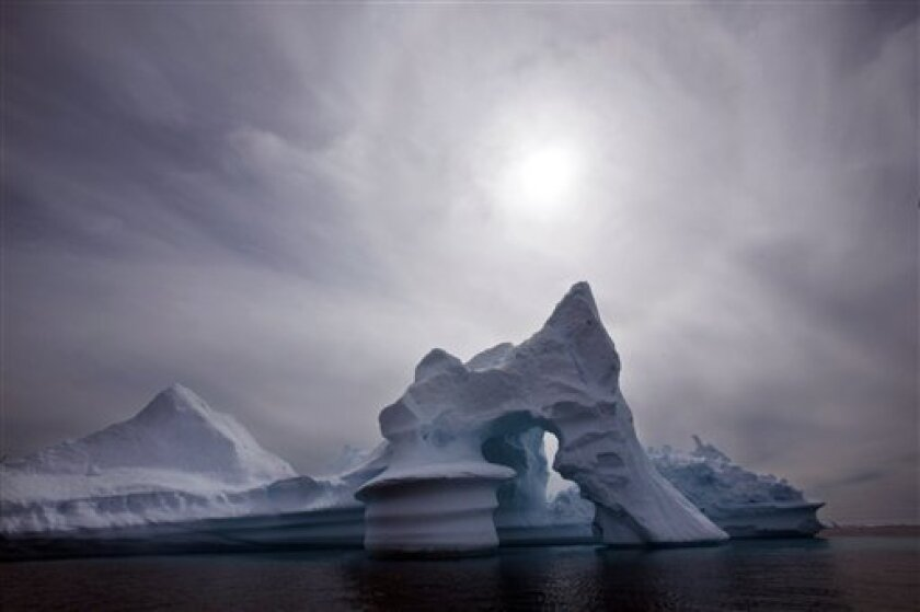 FILE - In this July 19, 2007 file photo an iceberg is seen off Ammassalik Island in Eastern Greenland.  A new assessment of climate change in the Arctic shows the ice in the region is melting faster than previously thought and sharply raises projections of global sea level rise this century. (AP Ph