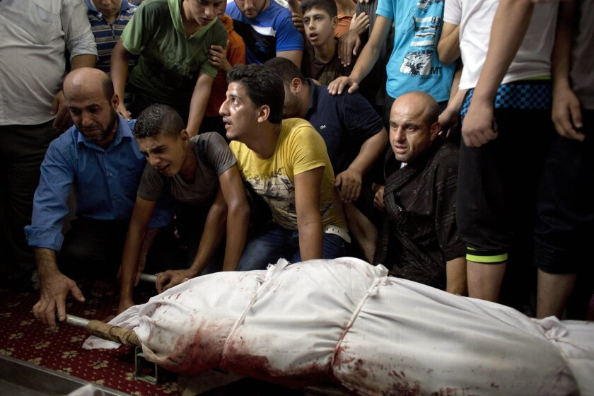 FILE - In this Monday Aug. 4, 2014 file photo, Palestinians mourn over the bodies of Najam family members who were killed overnight during their funeral in Beit Lahiya, Gaza Strip. Seven members of the Najam family, including a 90-year-old man and at least two children, perished in Sunday night's Israeli airstrike, the latest in more than a dozen similar attacks in this war that has, in some cases, wiped out two or three dozen members of a single extended family. (AP Photo/Dusan Vranic, File)