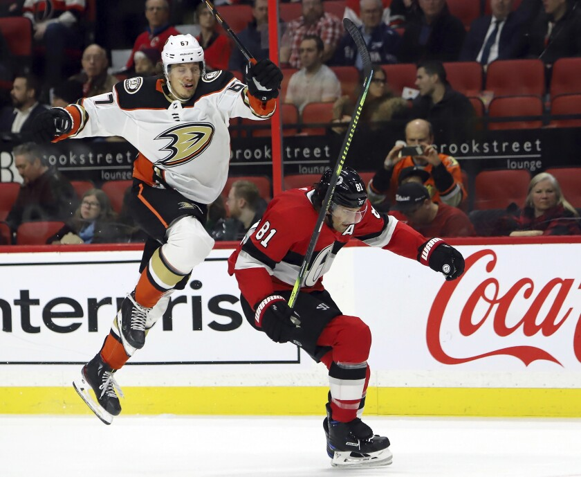 Anaheim Ducks left wing Rickard Rakell (67) avoids a hit from Ottawa Senators defenseman Ron Hainsey (81) during the first period of an NHL hockey game, Tuesday, Feb. 4, 2020 in Ottawa, Ontario. (Fred Chartrand/The Canadian Press via AP)