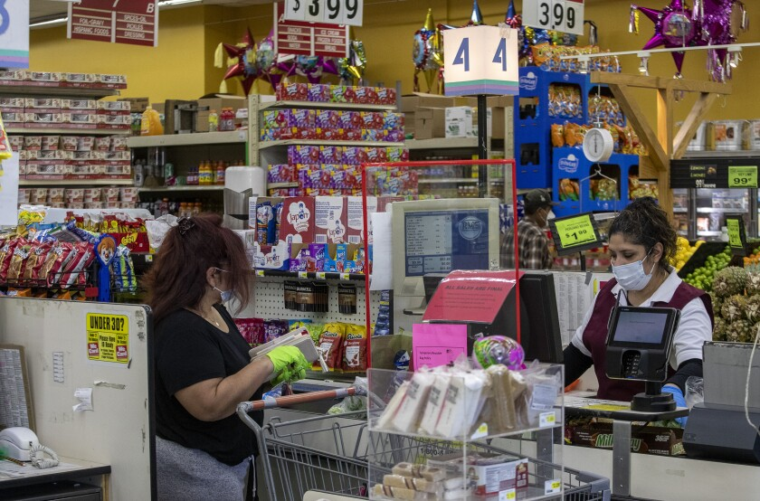 A supermarket cashier scans grocery items at the Advance Food Market in the West Adams neighborhood of Los Angeles.