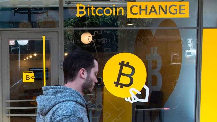 A man walks past the Bitcoin Change cryptocurrency shop in Tel Aviv, Israel.